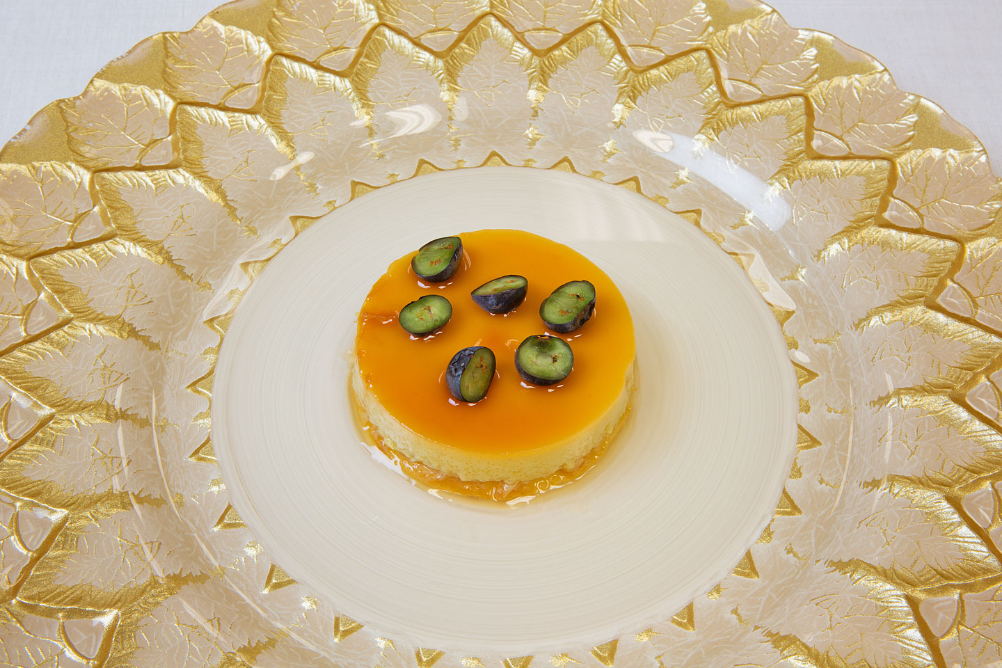 a delicious caramel flan dessert centered on a beautiful Florence charger plate, photographed by Jacob Rosenfeld