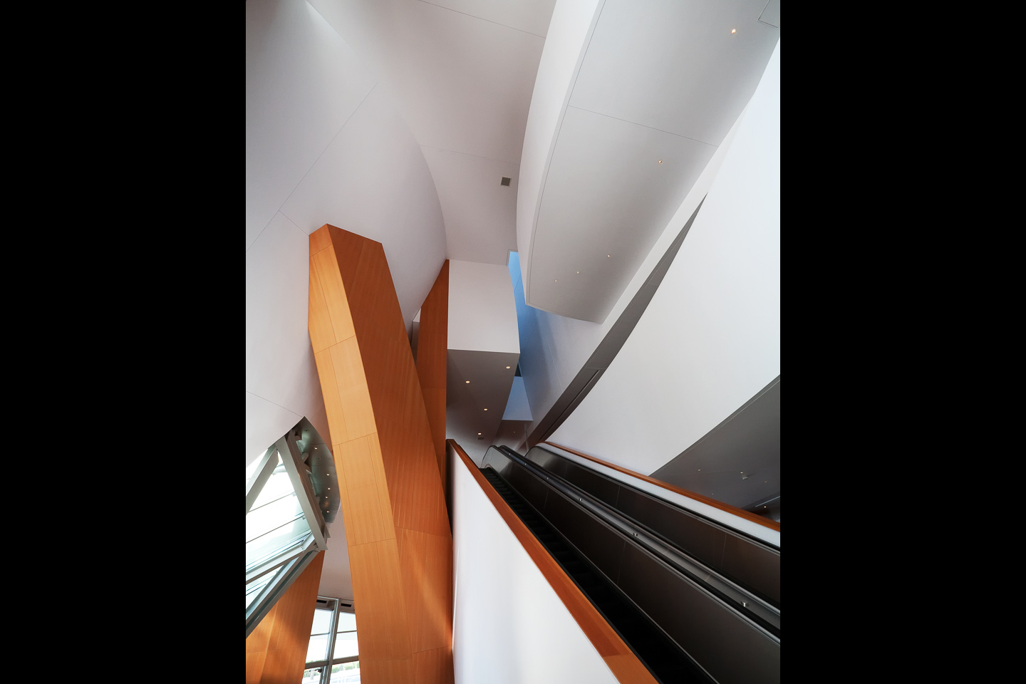 escalators, undulating lobby ceilings and soaring wood columns inside the Walt Disney Concert Hall, photographed by Jacob Rosenfeld
