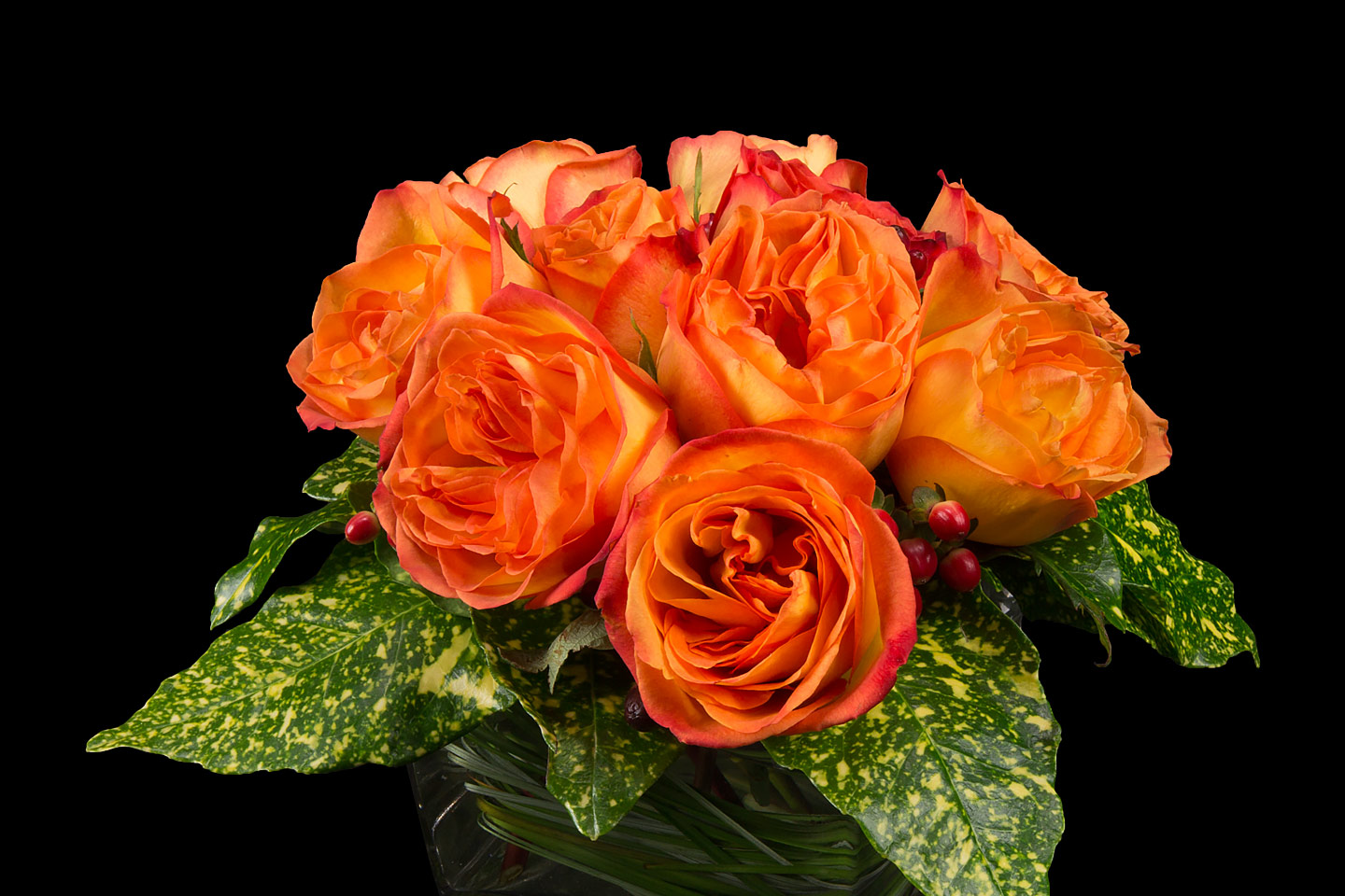 a bouquet of orange and yellow roses in a petite vase with pothos leaves, photographed by Jacob Rosenfeld
