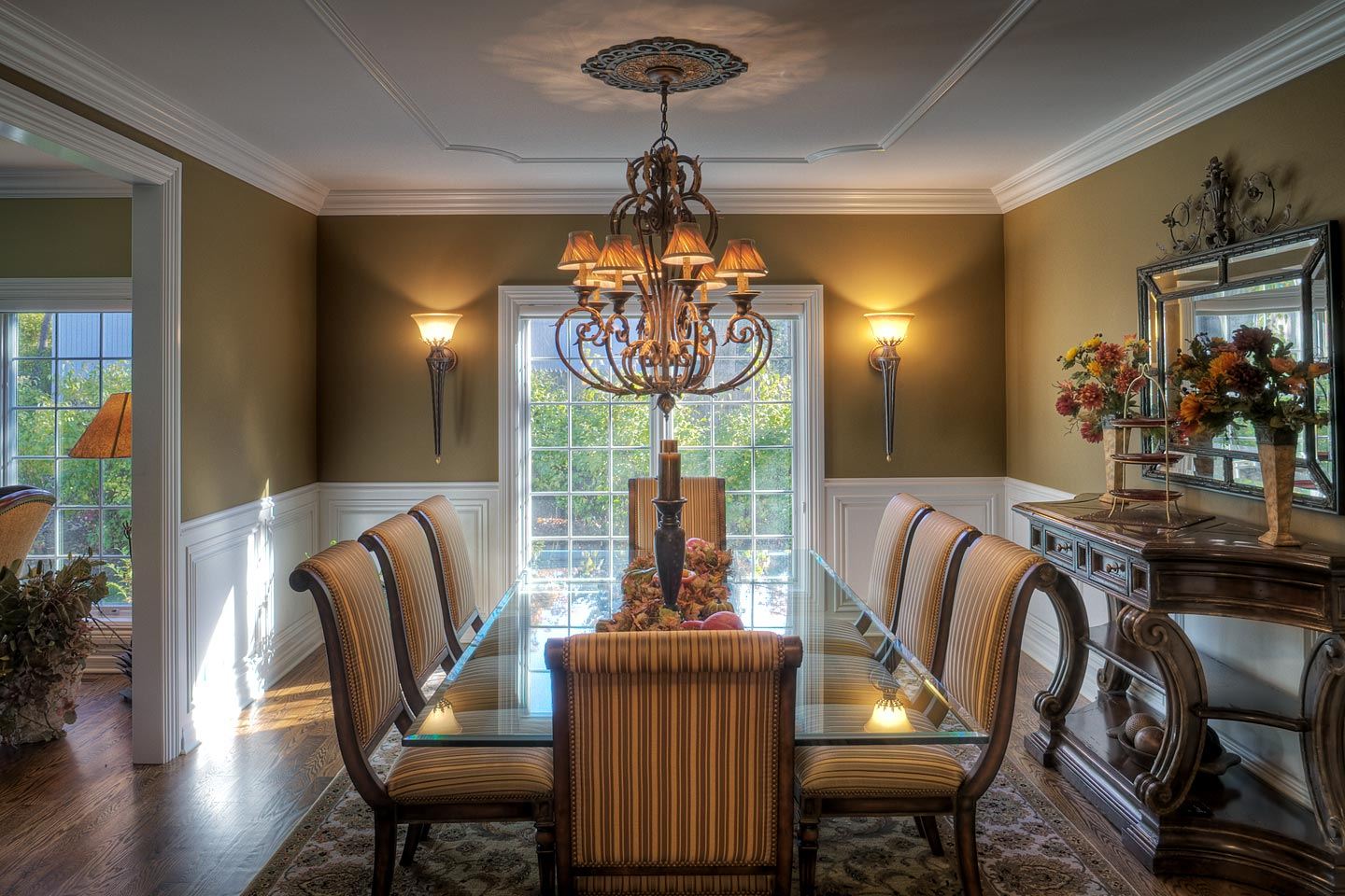 a beautifully decorated formal dining room featuring wainscoting and a long glass dining room table, photographed by Jacob Rosenfeld