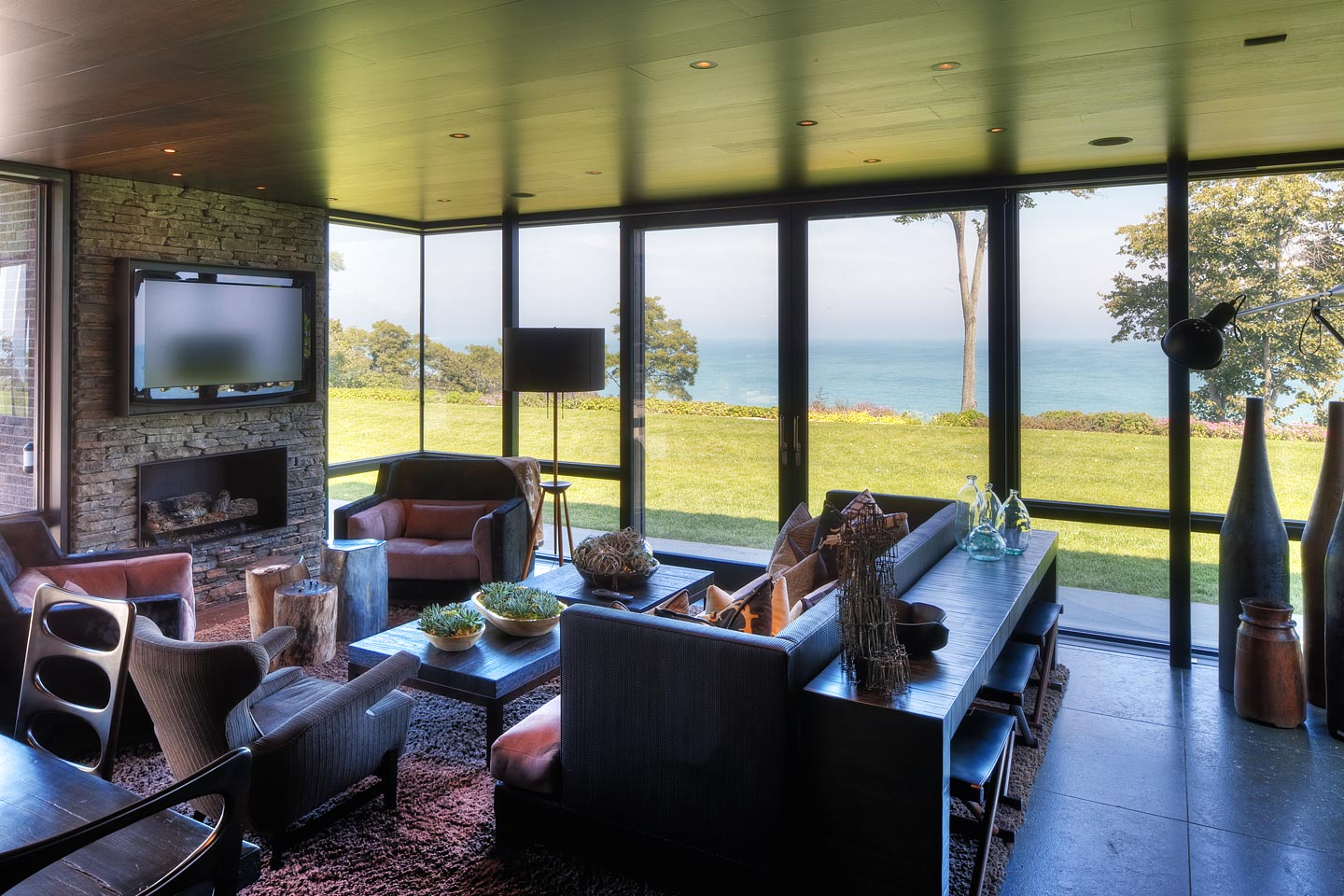 a modern glass den addition adjacent to the kitchen, featuring stunning views of Lake Michigan, photographed by Jacob Rosenfeld