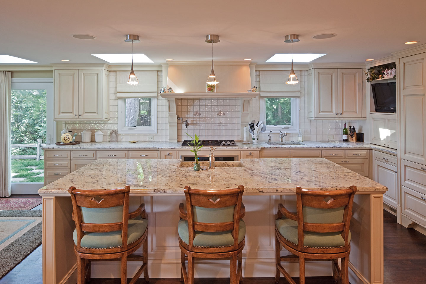 a panorama of a large modern kitchen, featuring a huge granite topped island and lots of cabinets, photographed by Jacob Rosenfeld