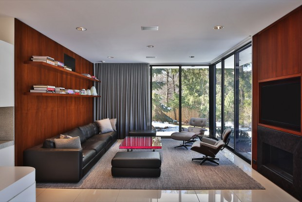 a glass enclosed living room, featuring warm wood paneling and ultra modern furniture, photographed by Jacob Rosenfeld