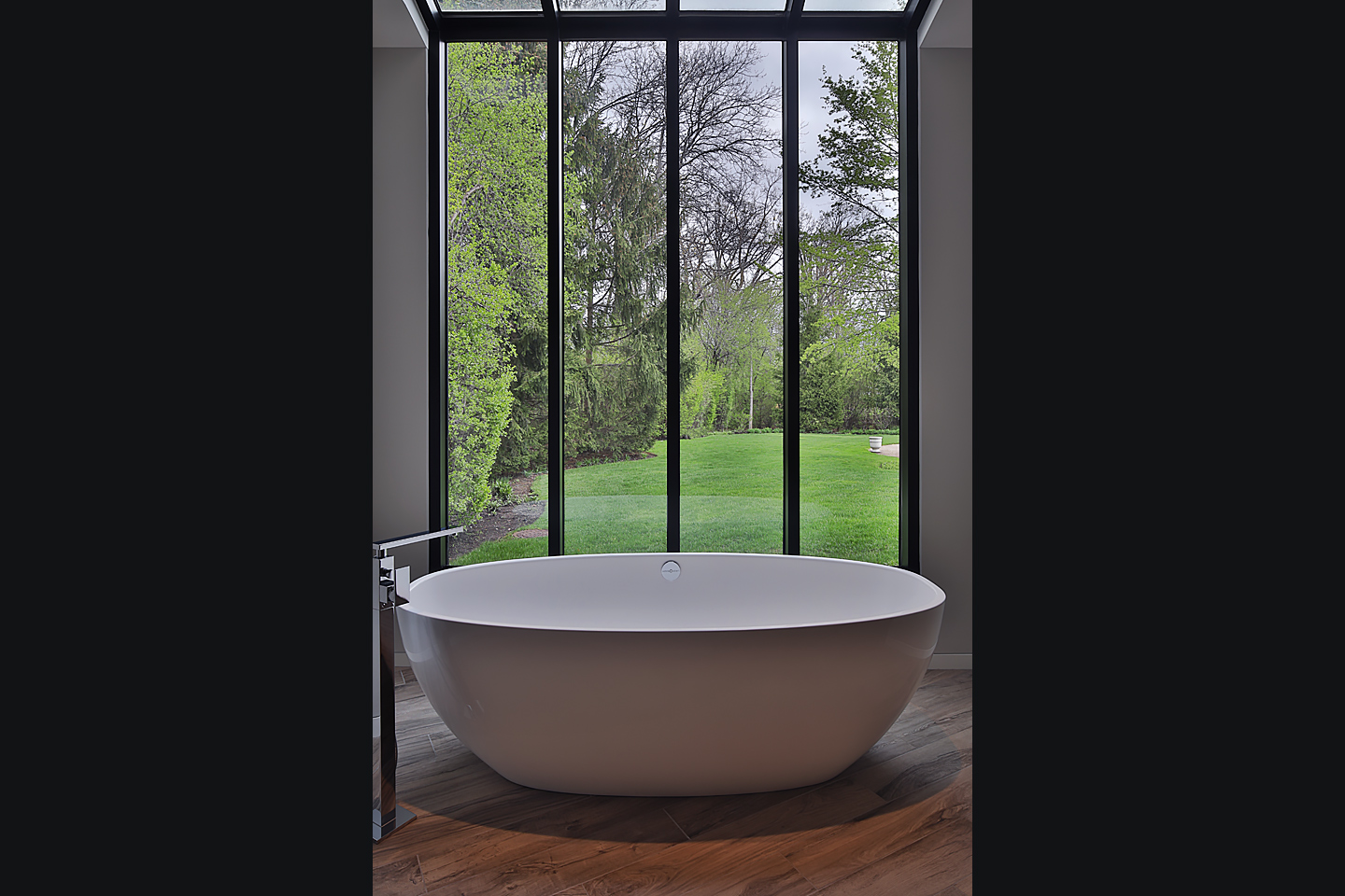 a modern master bath, freestanding tub sitting beside a large bank of windows, photographed by Jacob Rosenfeld